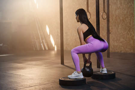 Young fit woman doing exercise with dumbbells in the gym.