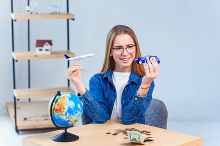 Girl holds airplane and car models in hands and choosing best transportation for trip.Travel around the world for your colorful life. Stockfoto