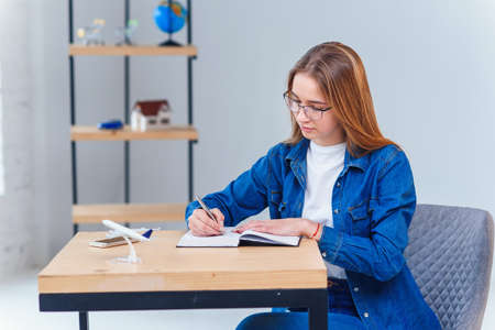 Beautiful young woman in office wearing denim clothes, make some notes on note book. Stockfoto