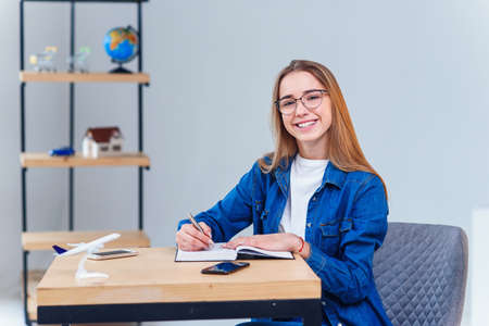 Smiling hipster girl in eyeglasses works and makes some notes and looking at camera. Stockfoto - 130220432