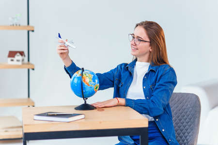 Beautiful woman dreaming about vacation. Girl holds in hand a model of airplane and flies around small globe. Stockfoto