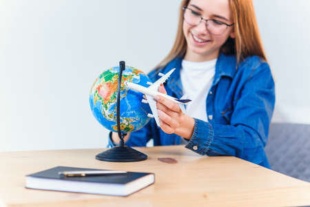 Young smiling woman holds in hand airplane model. Happy beautiful girl planning vacation trip. Stockfoto