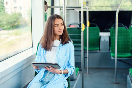Happy smiling woman reads a tablet or ebook in a modern tram or subway. Pretty girl rides for work in public transport. Stockfoto - 130220488