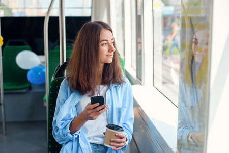 Pretty female passenger sits with smartp hone while moving in the modern tram or subway. Trip at the public transport. Stockfoto