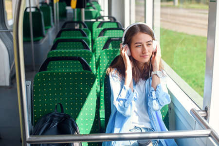 Female passenger listens to the music while traveling in a modern city tram and looks through the window Stockfoto