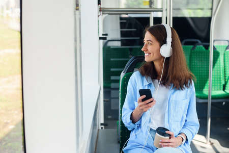 Young woman sits in the modern city bus, listens to music, drinks coffee and looks out from the window. Stockfoto