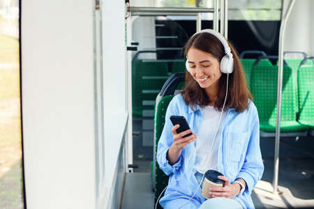 Young woman using public transport sits with smart phone and white headphones in the modern bus. Stockfoto
