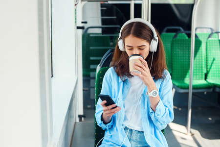 A beautiful girl sits in the modern city tram or subway, listens to music and drinks coffee.