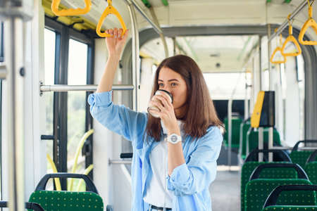 Beautiful woman in blue shit drinks coffee while riding in the public transport.