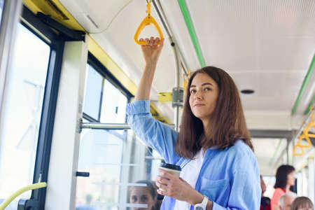 Beautiful young woman drinks delicious coffee in city bus or tram. Concept of public transport.