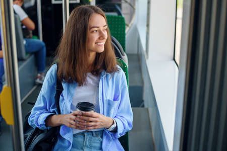 Beautiful girl with cup of delicious coffee rides to the university in public transport. Stockfoto