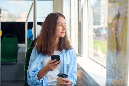 Pretty female passenger sits with smartp hone while moving in the modern tram or subway. Trip at the public transport. Stockfoto - 130220537