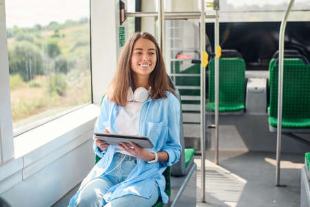 Happy smiling woman reads a tablet or ebook in a modern tram or subway. Pretty girl rides for work in public transport. Stockfoto
