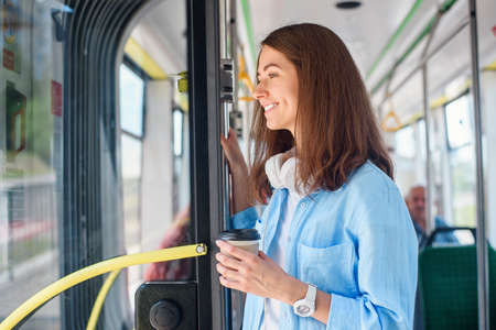Stylish woman in blue shirt enjoying trip in the modern tram or bus, stands with cup of coffee in the public transport. Stockfoto