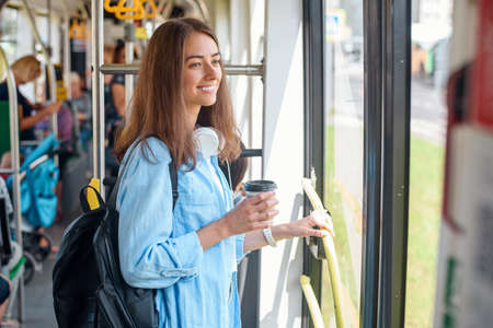 Stylish woman in blue shirt enjoying trip in the modern tram or bus, stands with cup of coffee in the public transport. Stockfoto - 130220535