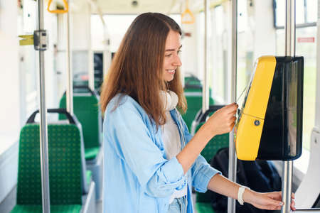 Young woman pays by bank card for the public transport in the tram or subway.