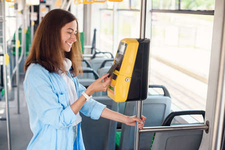 Female traveler pays contactless with bank card for the public transport in the tram or subway.