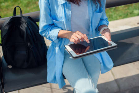 Female hand uses a tablet while waits on a public transport station. Stockfoto - 130220543