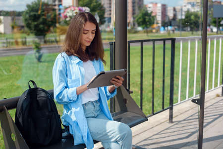 Happy woman uses a tablet or ebook on a tram station while waiting for public transport.