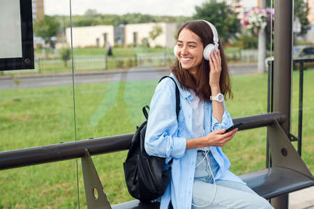 Teen girl listens to the music by white headphones in a public transport station while she waiting for tram.