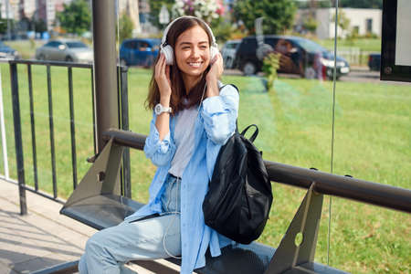 Teen girl listens to the music by white headphones in a public transport station while she waiting for tram. Stockfoto - 130220652