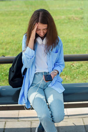 Young girl has broken down smartphone. Broken phone screen. Stockfoto - 130220655