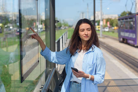 Stylish girl looks to map of public transport to find the right station while standing at the modern tram station outdoors