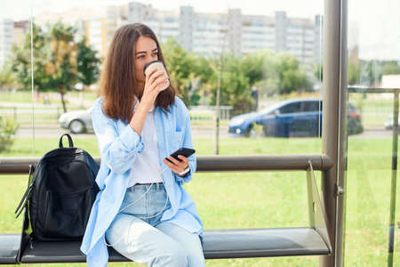 Charming hipster girl waiting for bus or tram on public transport station in the morning with cup of coffee and uses smart phone and internet to monitoring transport through the app.