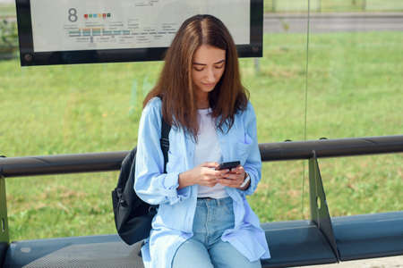 Charming girl with trendy look use smart phone while waiting on bus stop. Woman holds mobile phone while sitting on a public station and waiting for taxi. Stockfoto
