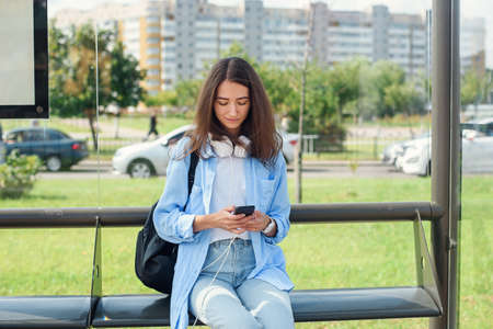 Charming girl with trendy look use smart phone while waiting on bus stop. Woman holds mobile phone while sitting on a public station and waiting for taxi. Фото со стока