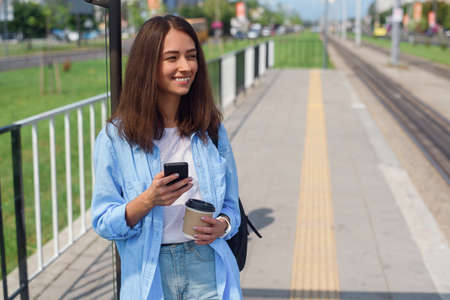 Pretty woman uses smart phone and drinks morning coffee to go while waiting tram or bus on the public station. Stockfoto - 130221970