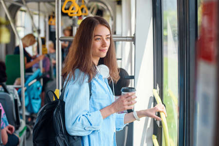 Young woman in blue shirt rides in the modern tram or bus with cup of coffee to go.