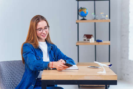 Woman dressed in denim shirt sits at the table during planning vacation trip uses smart phone. Stockfoto - 130222009