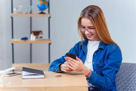 Woman dressed in denim shirt sits at the table during planning vacation trip uses smart phone. Stockfoto