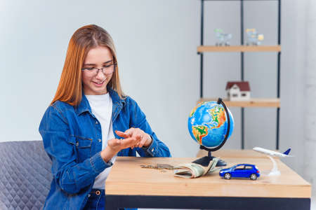 Beautiful caucasian girl counts her savings to foreign vacation. Young woman sits at table with glass jar, money, globe, model of air plane and car.