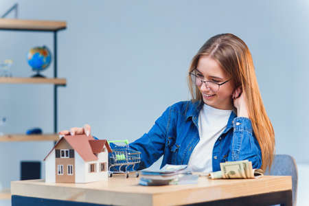 Young pretty girl counts her savings money and looks to a model of the house.