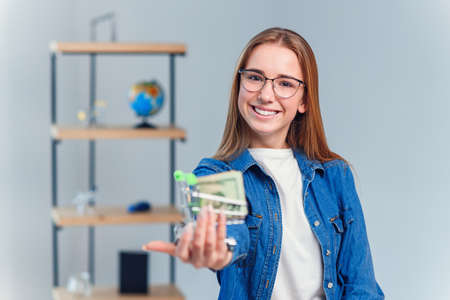 Young beautiful woman in denim shirt and eyeglasses holds small shopping cart full of US dollar. Shopping, saving money concept.