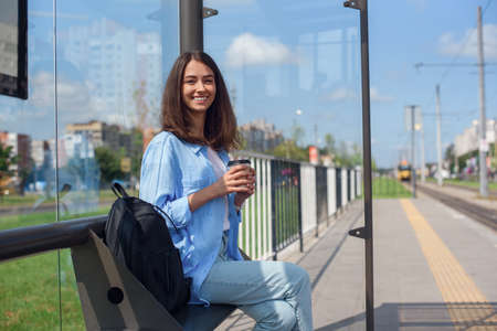 Beautiful girl waits for subway or tram on public transport station in the morning. Happy young woman with cup of coffee on public station.
