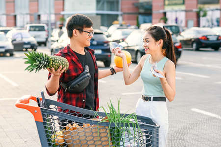 Likable asian couple standing near shopping cart,man holds pineapple and melon and beautiful woman counts the banknotes of usa dollars.