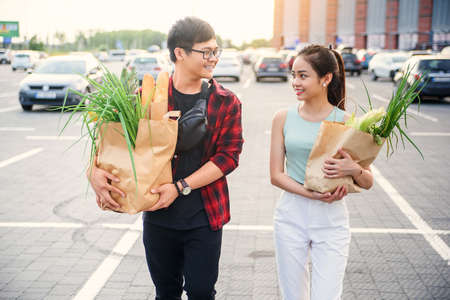 Handsome smiling guy in glasses and cute slender girl go with two big paper bags full of various products purchased in the store
