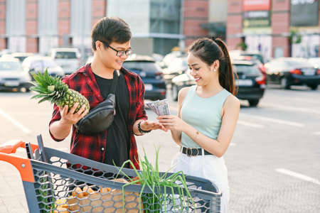 Smiling asian couple standing near shopping cart,man holds pineapple and cheerful woman counts the banknotes