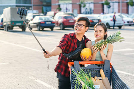 Young asian couple holding in their hands pineapple and melon and making selfie photo. Zdjęcie Seryjne
