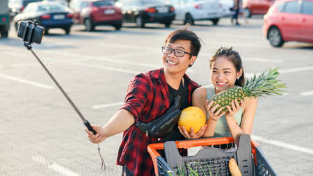 Young asian couple holding in their hands pineapple and melon and making selfie photo. Zdjęcie Seryjne - 131784762