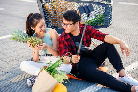 Happy vietnamese couple sitting on the ground near big shopping centre and making selfie photo with peanapple. Banco de Imagens