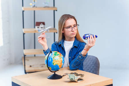Young woman holds a model of air plane and car and chooses better transportation for travel. Travel and vacation concept.