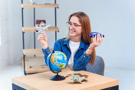 Young woman holds a model of air plane and car and chooses better transportation for travel. Travel and vacation concept. Standard-Bild