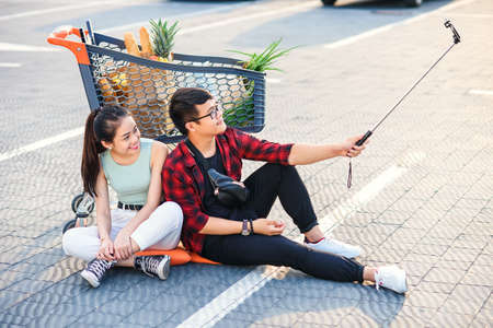 Stylish young vietnamese couple sitting on the ground near shopping trolley and making selfie photo together.