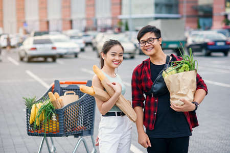 Likable asian couple hold paper eco bags with organic healthy food in hands while standing near store mall. Happy family shopping on weekend.