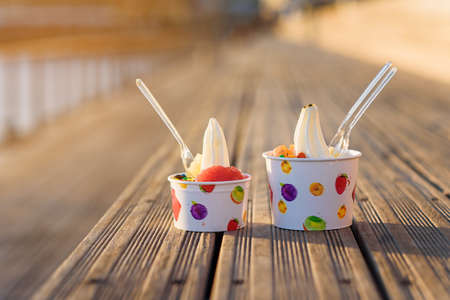 Two cups of ice cream with candies on sunset. Banque d'images - 131784555