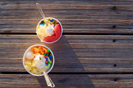 Two cups of ice cream with candies on sunset. Banque d'images - 131784607